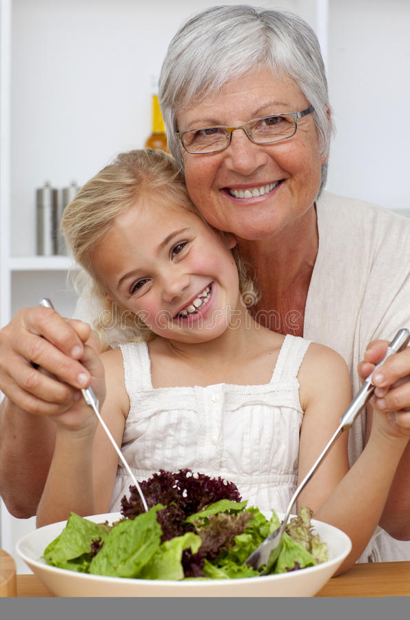 Grandmother eating a salad with granddaughter