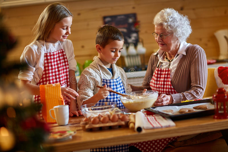 Grandmother enjoying with children making Christmas cookies stock photo