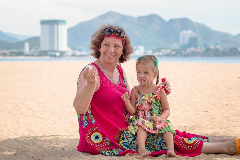 Grandmother enjoying day with granddaughter while blowing soap bubbles on the beach near the sea.  royalty free stock photography