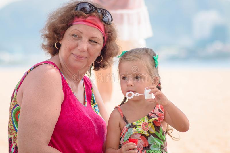 Grandmother enjoying day with granddaughter while blowing soap bubbles on the beach near the sea.  royalty free stock photos