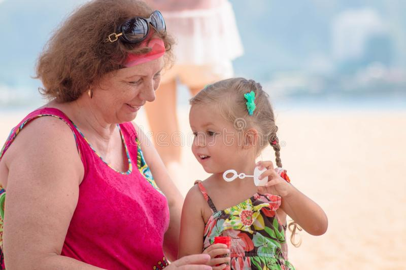 Grandmother enjoying day with granddaughter while blowing soap bubbles on the beach near the sea.  stock photos