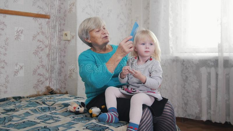 Grandmother enjoys combing hair to child on sunny morning. Good time at home. Baby sitting on granny`s laps. Portrait royalty free stock photos