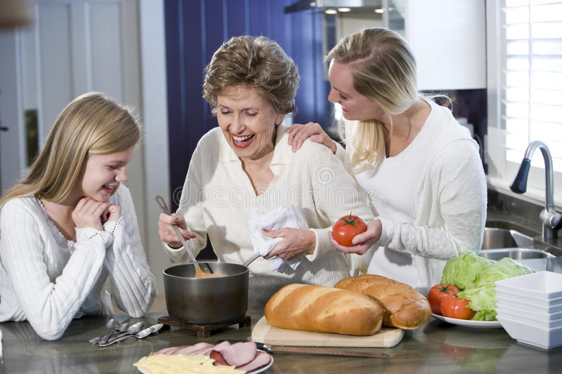 Grandmother with family cooking in kitchen. Smiling and laughing together stock photography