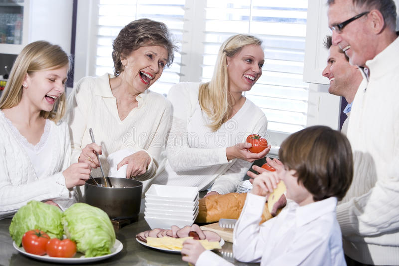 Grandmother with family laughing in kitchen. Grandmother with family cooking in kitchen, smiling and laughing together royalty free stock photography