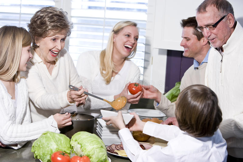 Grandmother with family laughing in kitchen. Grandmother with family cooking in kitchen, smiling and laughing together royalty free stock image