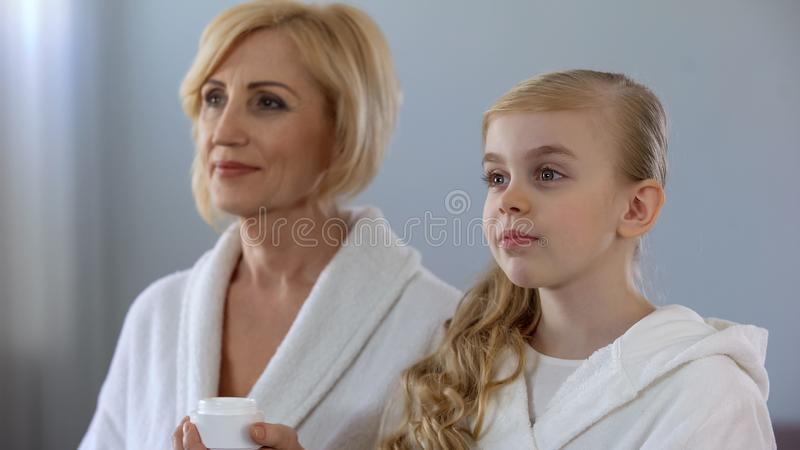 Grandmother and grandchild going to apply face cream, skin care, beauty stock photography