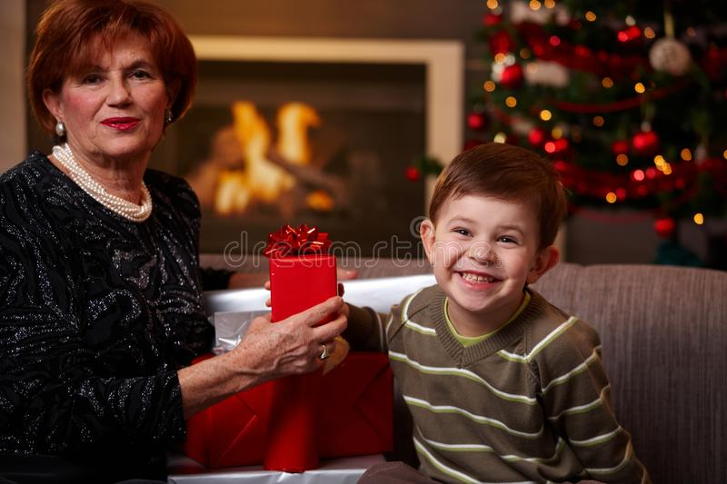 Grandmother and grandchild holding gift. Happy grandmother and grandchild sitting on sofa at home, holding christmas gift, smiling royalty free stock images