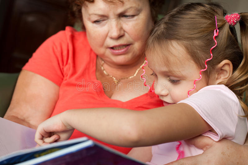 Grandmother and grandchild reading stock photo