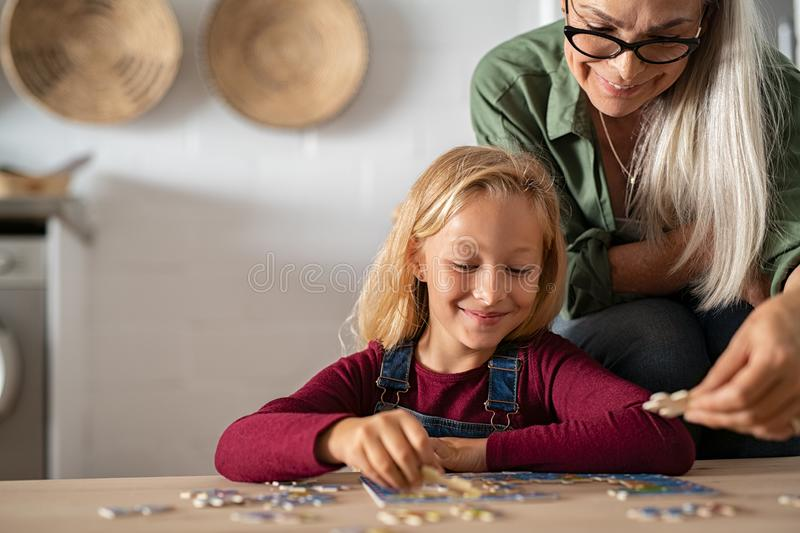Grandmother and grandchild solving jigsaw puzzle. Grandmother and granddaughter doing jigsaw puzzle together at home. Senior women helping smiling little girl to stock images
