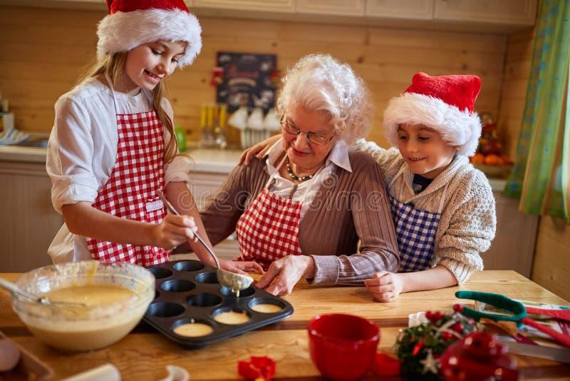 Grandmother and grandchildren preparing cookies -Family time stock photo