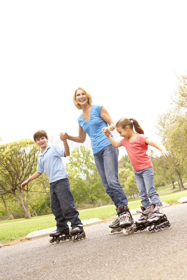 Grandmother And Grandchildren Skating In Park stock photos