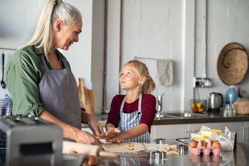 Grandmother and granddaughter cooking together royalty free stock images