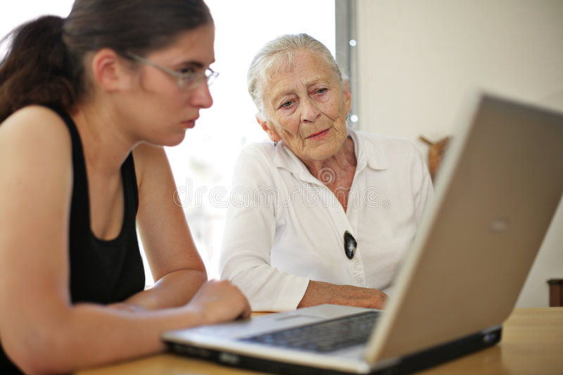 Grandmother and granddaughter at copmuter stock photo