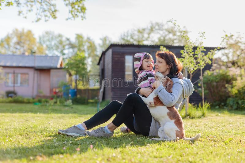 Grandmother with granddaughter and dog playing on the sunbathing lawn. Sunny spring day in the village royalty free stock photos