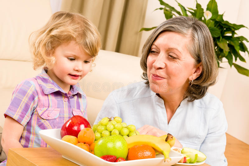 Download Grandmother With Granddaughter Eat Fruit At Home Stock Photo - Image: 23458934