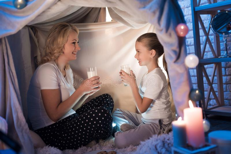 Grandmother and granddaughter are eating cookies with milk in blanket house at night at home. stock image