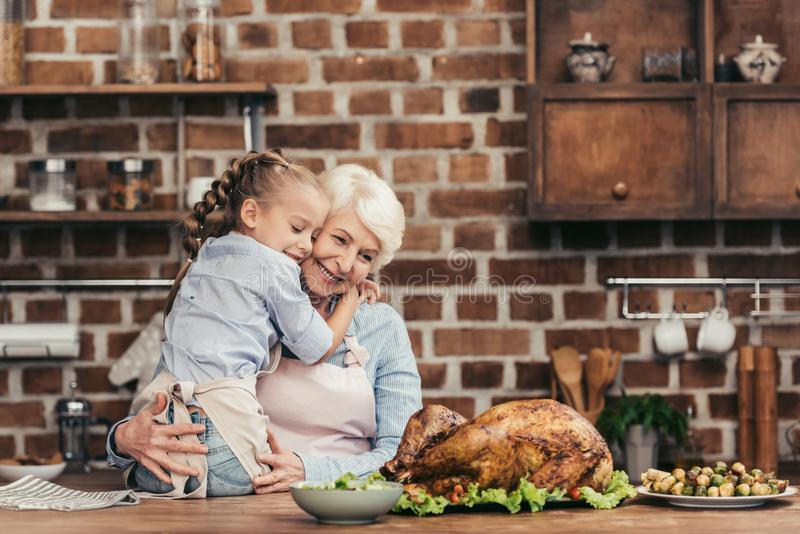 Grandmother and granddaughter embracing on kitchen and looking at freshly prepared turkey. For thanksgiving dinner stock photo