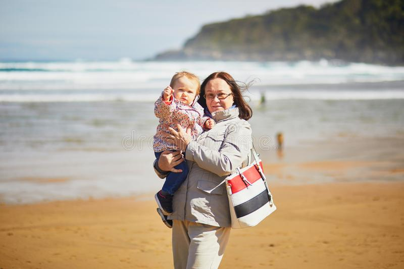 Grandmother and granddaughter enjoying Atlantic ocean on the beach. Middle aged women holding little girl on the sea shore. Tourists on La Concha beach in San royalty free stock photo