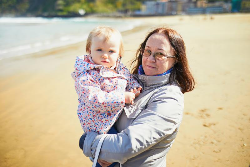 Grandmother and granddaughter enjoying Atlantic ocean on the beach. Middle aged women holding little girl on the sea shore. Tourists on La Concha beach in San royalty free stock image