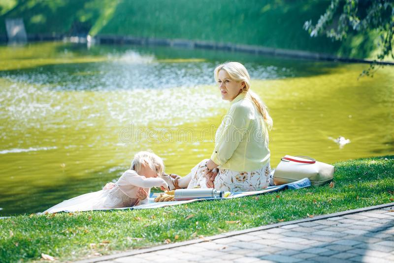 Grandmother and granddaughter enjoying picnic in a park near water. Grandma playing with little toddler girl in a sunny autumn for stock photography