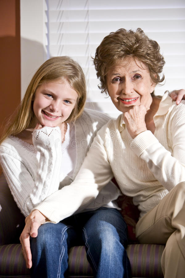 Grandmother and granddaughter in living room. Portrait of grandmother and granddaughter in living room royalty free stock photography