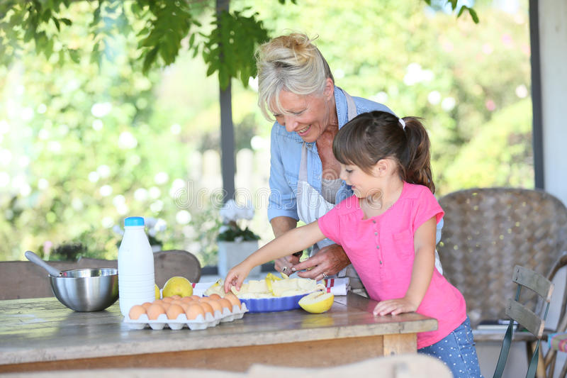 Grandmother and granddaughter making an apple pie royalty free stock photo