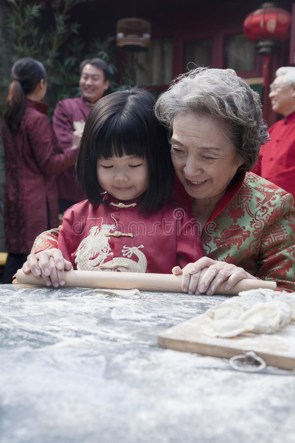 Grandmother and granddaughter making dumplings in traditional clothing stock images