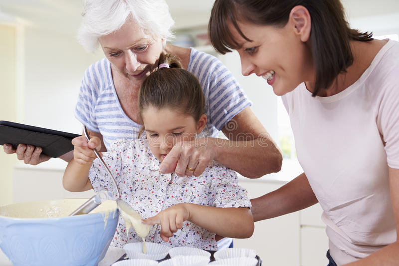 Grandmother, Granddaughter And Mother Baking Cake In Kitchen stock photo