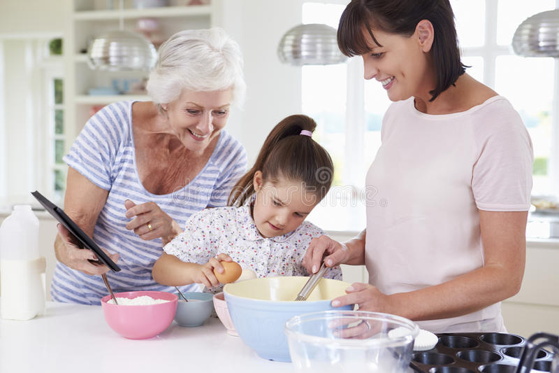 Grandmother, Granddaughter And Mother Baking Cake In Kitchen stock images