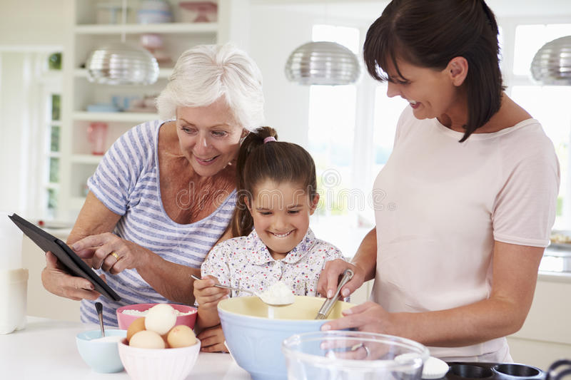 Grandmother, Granddaughter And Mother Baking Cake In Kitchen stock photography