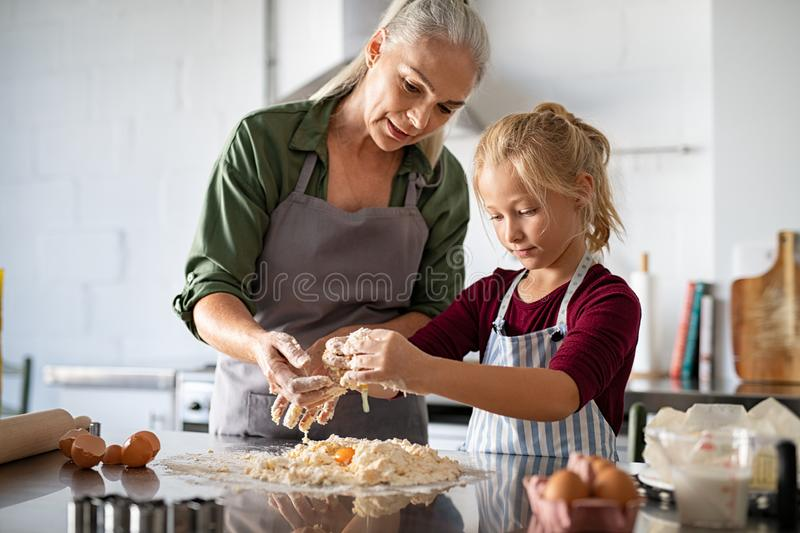 Grandmother and granddaughter preparing dough royalty free stock photography