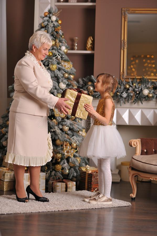 Grandmother and granddaughter present a gift near the Christmas stock image