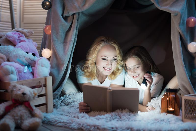 Grandmother and granddaughter are reading book in blanket house at night at home. stock photography