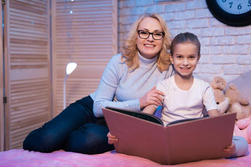 Grandmother and granddaughter are reading book at night at home. royalty free stock photos
