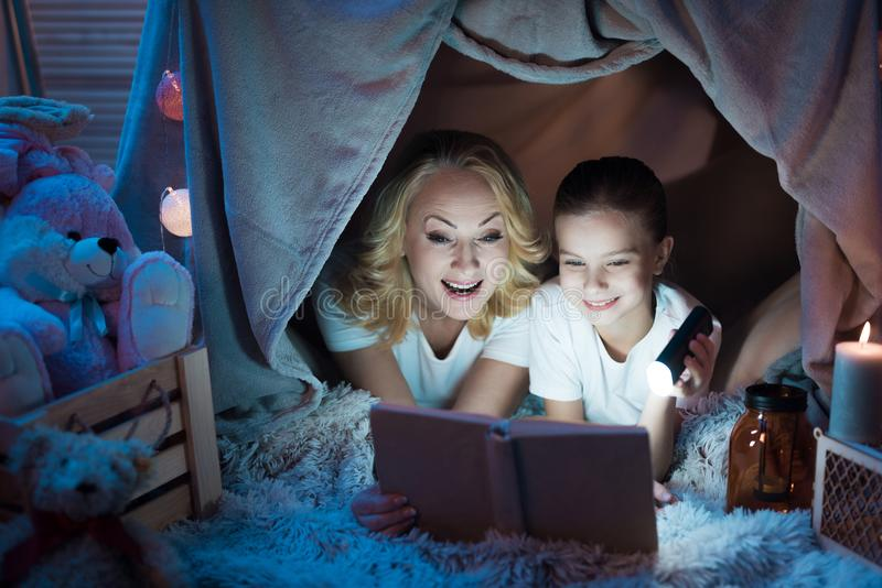 Grandmother and granddaughter are reading fairy tales in blanket house at night at home. stock photo