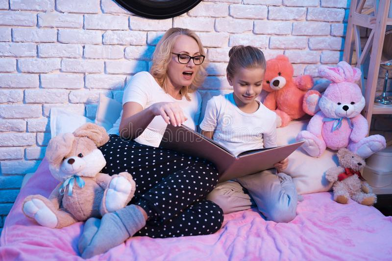 Grandmother and granddaughter are reading lange book at night at home. royalty free stock images