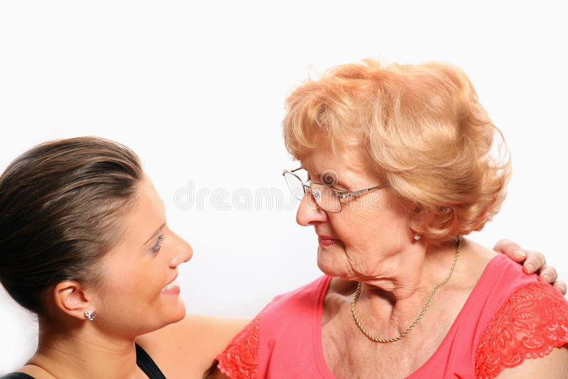 Grandmother and granddaughter talking. A picture of grandmother and granddaughter talking over white background stock photos