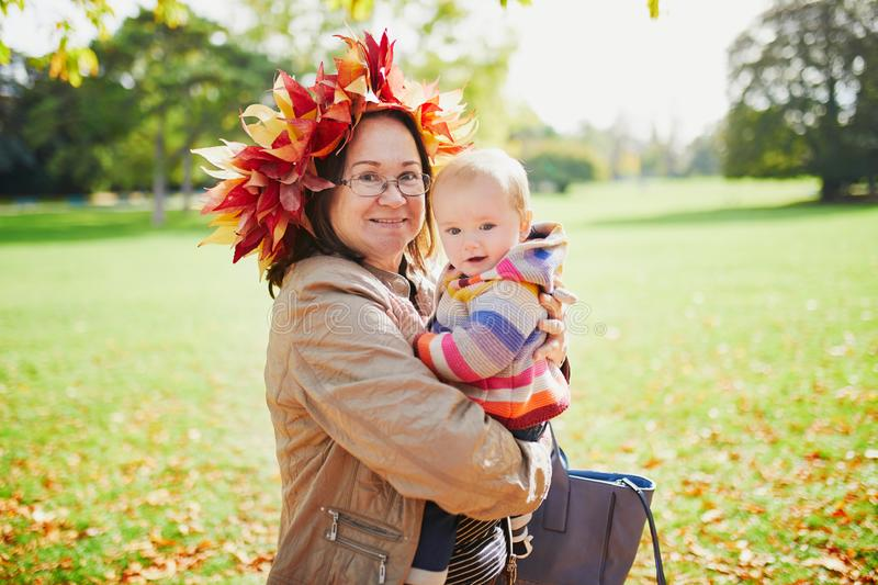 Grandmother and granddaughter together in autumn park. Happy middle aged women wearing maple leaves wreath with baby girl on sunny fall day in park. Grandmother stock photo