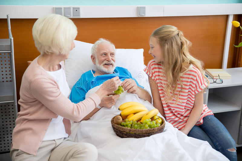 Grandmother and granddaughter visiting patient. Grandmother and granddaughter with fruits visiting patient in hospital. male patient in hospital bed concept stock photos