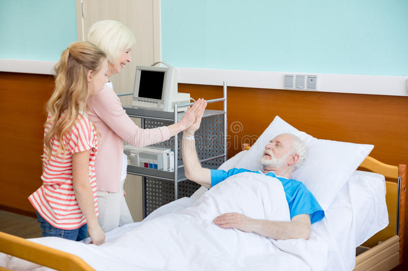Grandmother and granddaughter visiting patient. In hospital. male patient in hospital bed concept stock image