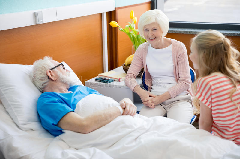 Grandmother and granddaughter visiting patient. In hospital. male patient in hospital bed concept royalty free stock photos