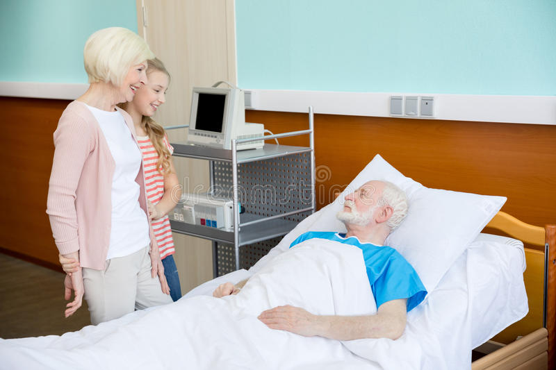 Grandmother and granddaughter visiting patient. In hospital. male patient in hospital bed concept royalty free stock images