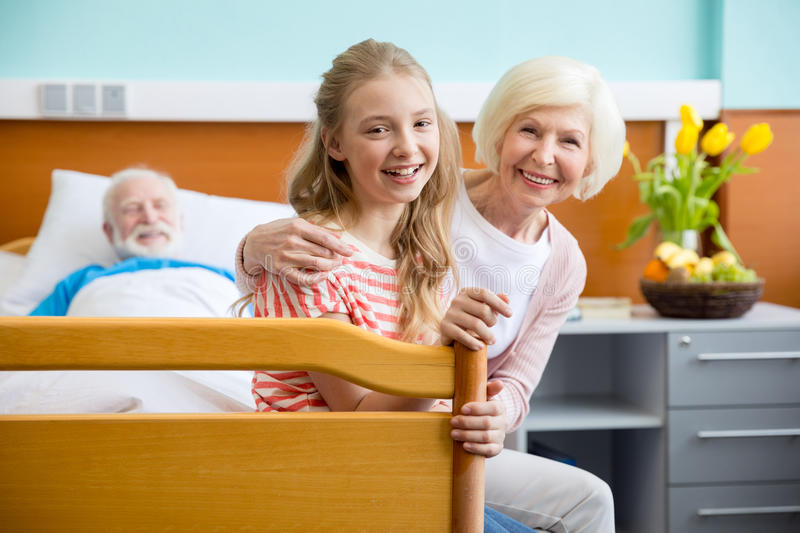 Grandmother and granddaughter visiting patient. Portrait of happy grandmother and granddaughter visiting patient in hospital royalty free stock photos