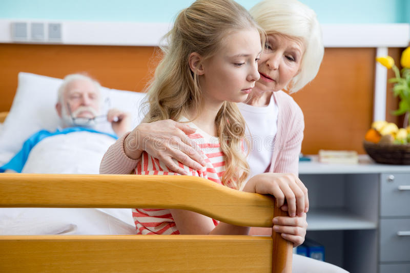 Grandmother and granddaughter visiting patient. Portrait of upset grandmother and granddaughter visiting patient in hospital royalty free stock images