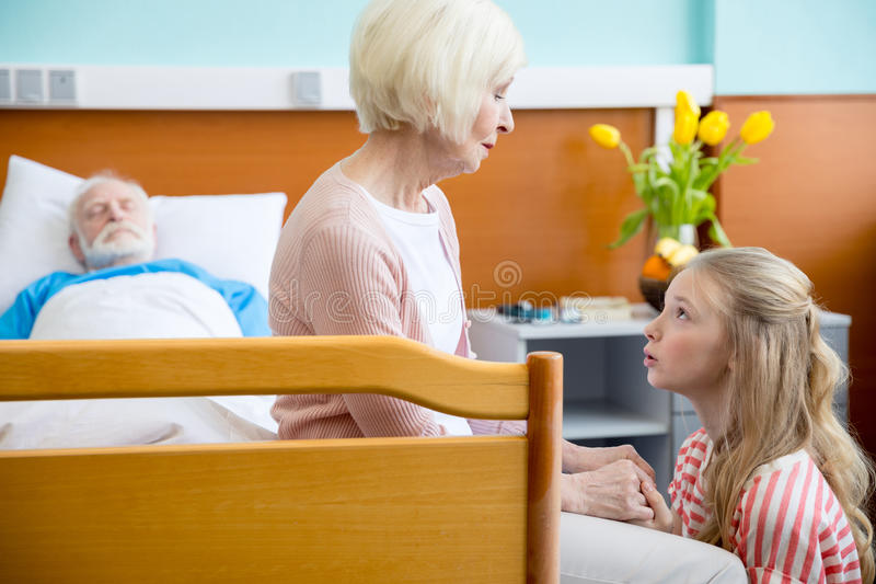 Grandmother and granddaughter visiting patient. Portrait of upset grandmother and granddaughter visiting patient in hospital royalty free stock photos