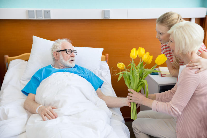 Grandmother and granddaughter visiting patient. Grandmother and granddaughter with tulip flowers visiting patient in hospital. male patient in hospital bed royalty free stock photos