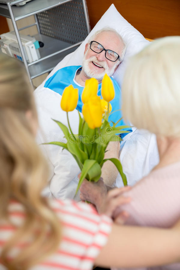 Grandmother and granddaughter visiting patient. Grandmother and granddaughter with tulip flowers visiting patient in hospital. male patient in hospital bed stock photo