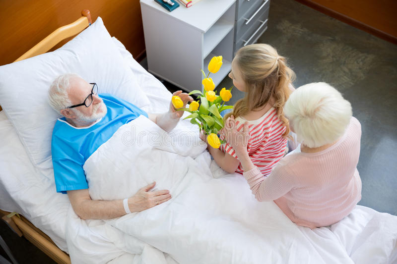 Grandmother and granddaughter visiting patient. Grandmother and granddaughter with tulip flowers visiting patient in hospital. male patient in hospital bed royalty free stock images