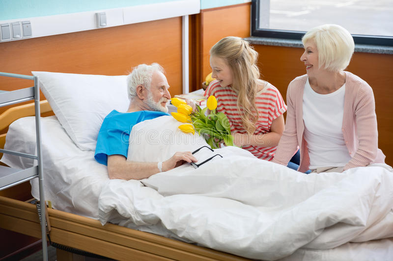 Grandmother and granddaughter visiting patient. Grandmother and granddaughter with tulip flowers visiting patient in hospital. male patient in hospital bed stock photos