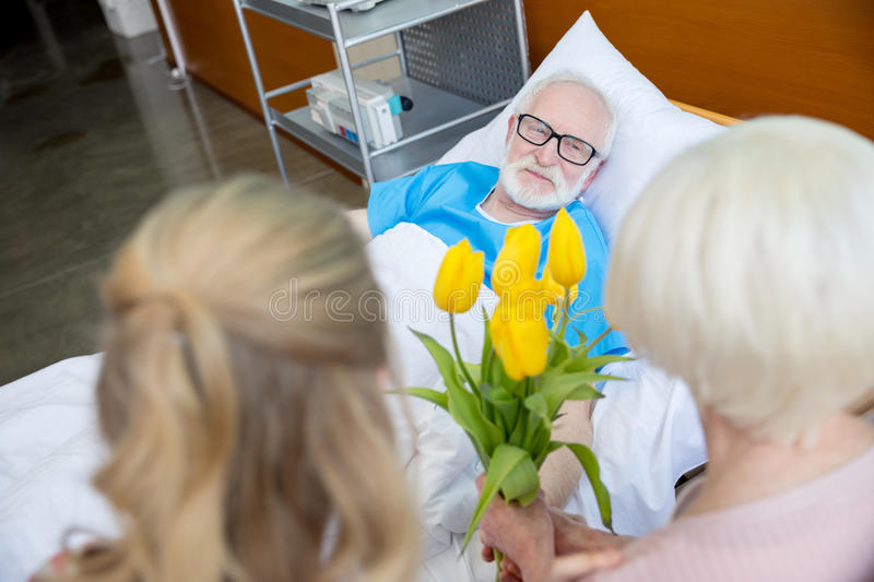 Grandmother and granddaughter visiting patient. Grandmother and granddaughter with tulip flowers visiting patient in hospital. male patient in hospital bed stock image